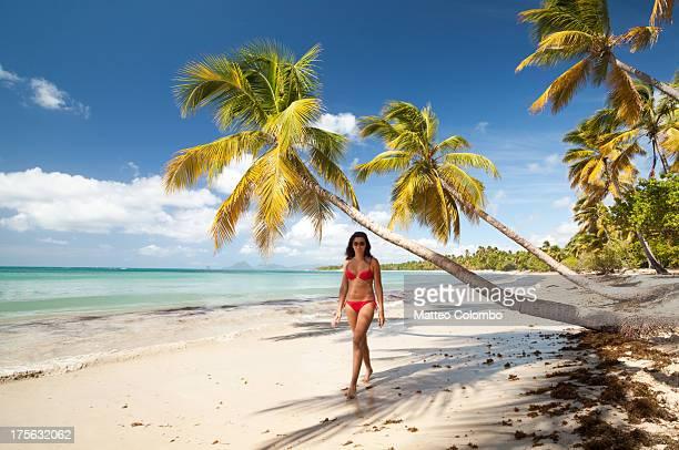 Woman in red bikini walking on tropical beach
