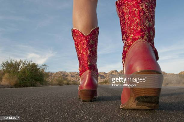 Woman in red boots walking to horizon
