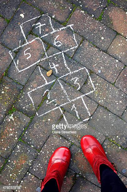 woman in red boots with a chalk hopscotch course - 赤の靴 ストックフォトと画像