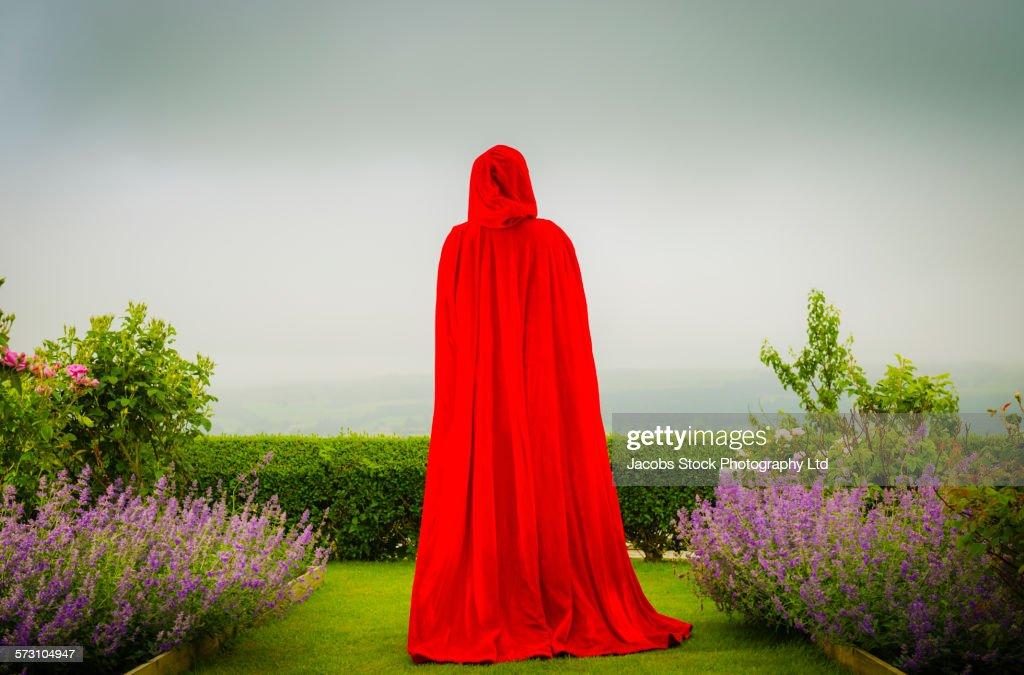 Woman in red cloak standing in garden : Stock Photo