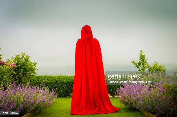 Woman in red cloak standing in garden