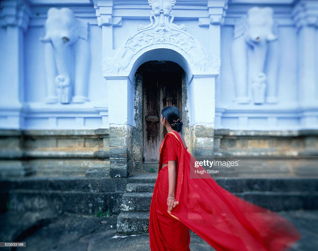 Woman in red clothes in front of temple, Sri Lanka : Stock Photo