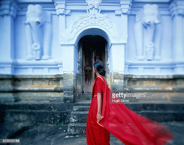 Woman in red clothes in front of temple, Sri Lanka