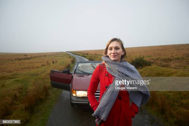 Woman in red coat and car on a country lane.