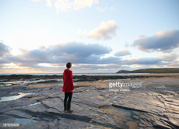 woman in red coat looking along coastline. - red coat stock pictures, royalty-free photos & images