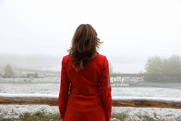 Woman in red coat overlooking snowy landscape