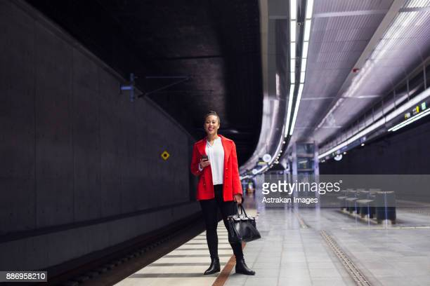 Woman in red coat standing and smiling at train station