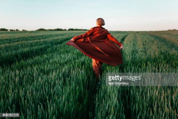woman in red coat  walking  in the field at sunset - kleid stock-fotos und bilder