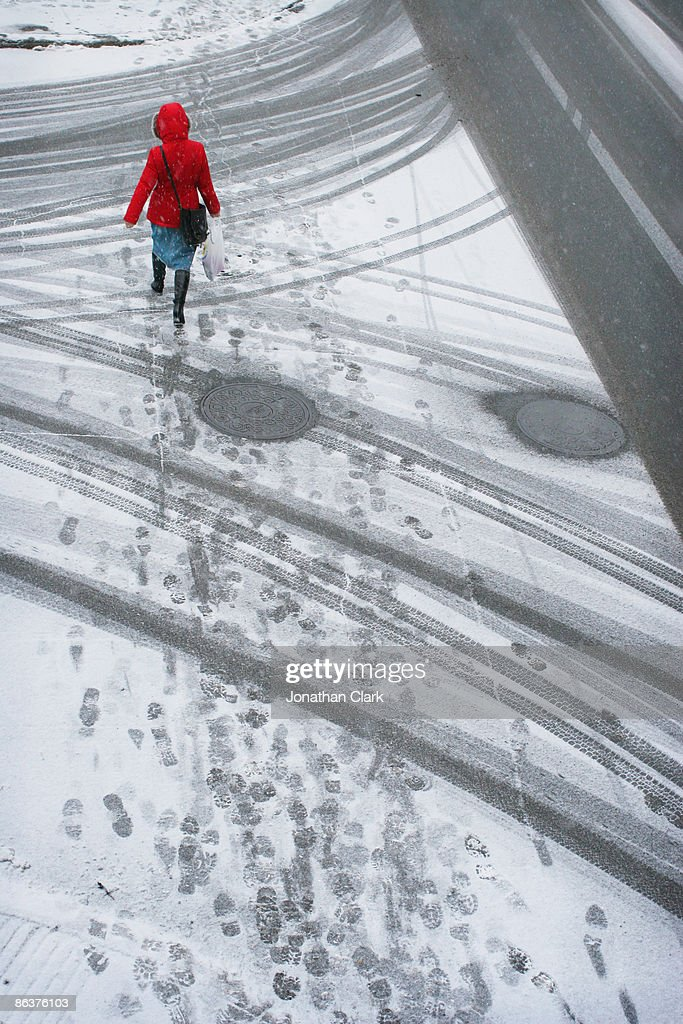 Woman in red coat walking in the snow : Stock Photo