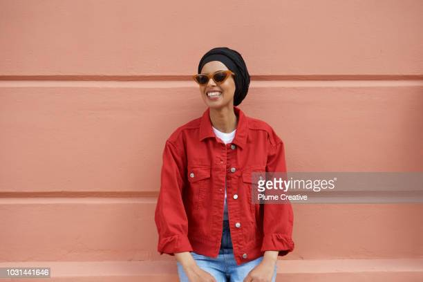 Woman in red denim jacket sitting on a peach coloured wall