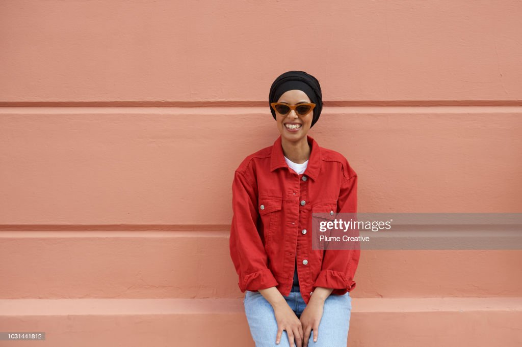 Woman In Red Denim Jacket Sitting On A Peach Coloured Wall Stock