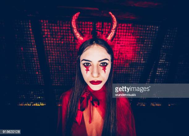 woman in red devil costume and dramatic make-up for halloween - devil costume stock photos and pictures
