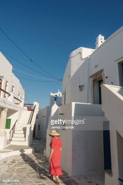Woman in red dress and straw hat walks though traditional white Greek houses (by church with crooked cross) in evening light casting a long shadow, Kastro Village, Sifnos, Cyclades Islands, Greece