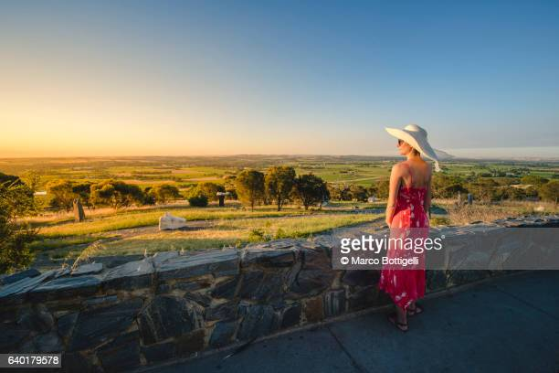 Woman in red dress and sun hat admiring the view at sunset over the Barossa Valley, South Australia, Australia.