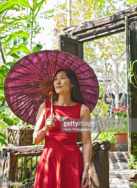 Woman in red dress at traditional Thai House