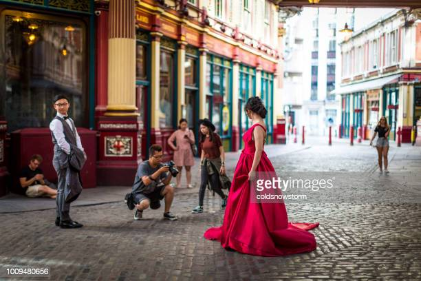 woman in red dress being photographed in leadenhall market, london, uk - leadenhall market stock photos and pictures