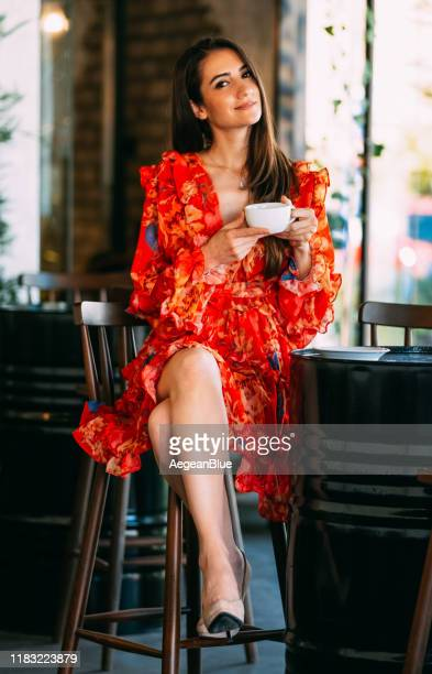 woman in red dress drinking coffee in cafe - red dress stock pictures, royalty-free photos & images