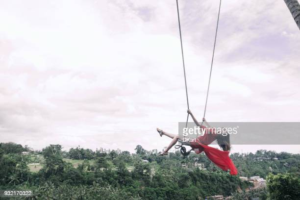 Femme en robe rouge, volant vers le haut le swing parmi la jungle de Bali