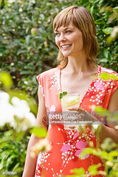 "woman in red dress holding drink and smiling - ""compassionate eye"" bildbanksfoton och bilder"