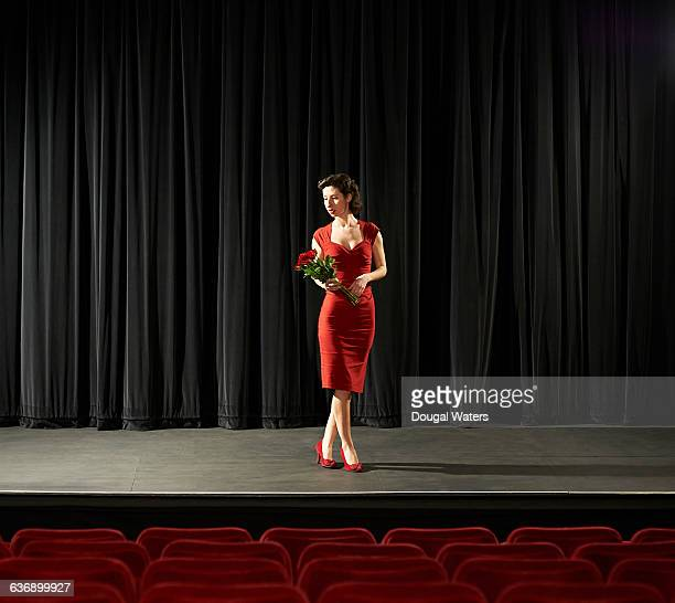 Woman in red dress holding roses on stage.