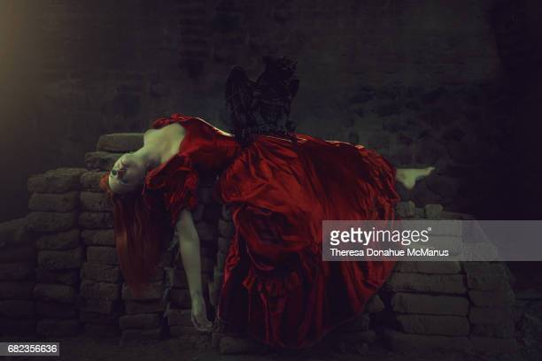 woman in red dress lying on a sacks of cement - demons stock photos and pictures