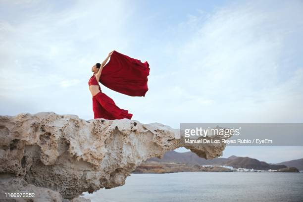 woman in red dress on rock formation - red dress stock pictures, royalty-free photos & images