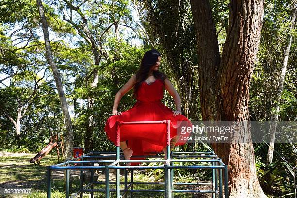 Woman In Red Dress Sitting On Jungle Gym At Park