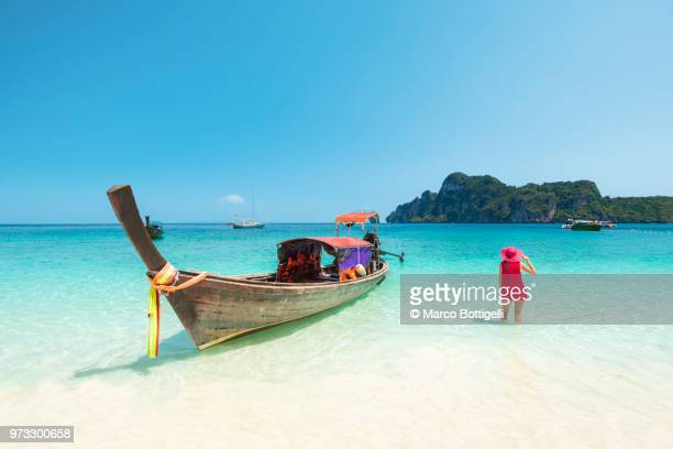 woman in red dress standing in water beside a longtail boat, thailand - phi phi islands stock-fotos und bilder