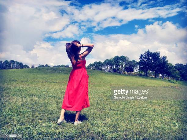woman in red dress standing on field. - 赤のドレス ストックフォトと画像