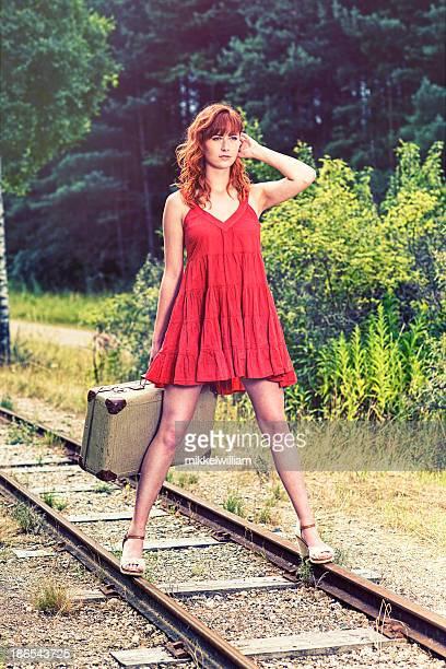 Frau im roten Kleid steht auf Bahngleise mit Koffer