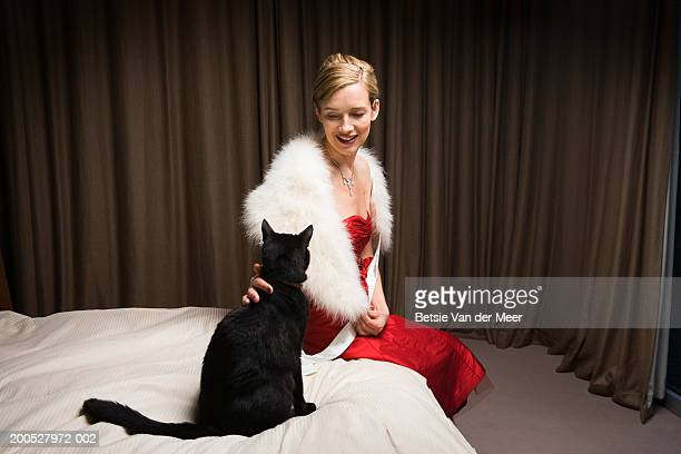 Woman in red dress stroking cat on bed, smiling