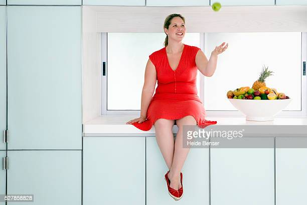 Woman in Red Dress Tossing Apple