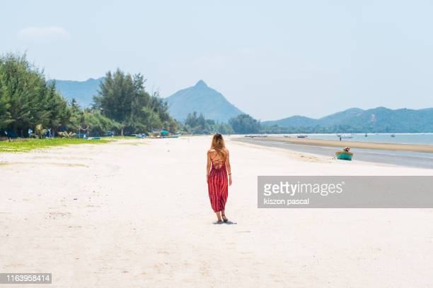 woman in red dress walking alone on the beach during a summer day . - prachuap khiri khan province stock pictures, royalty-free photos & images