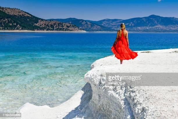 赤いドレスを着た女性が浜辺を歩いている。 - 赤のドレス ストックフォトと画像