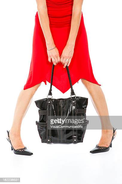 woman in red dress with black purse.