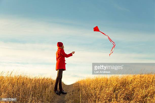 Woman in red flying a kite