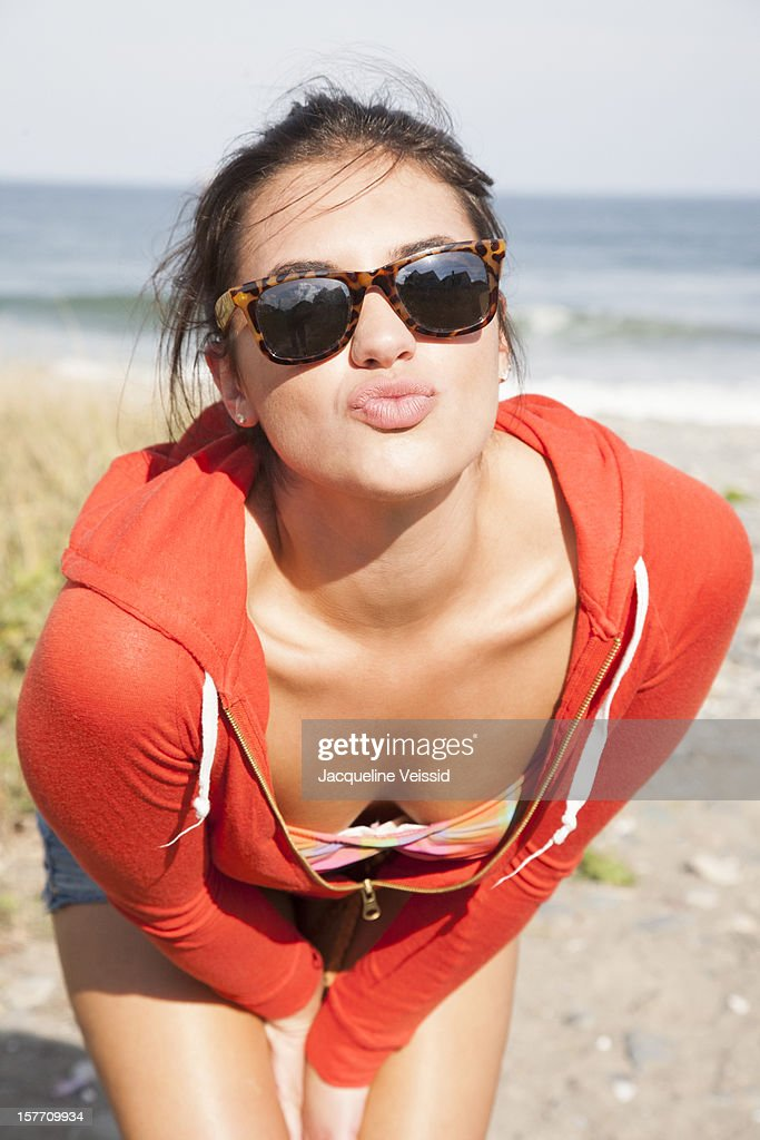 Woman in red hoodie on beach with kissing lips : Stock Photo