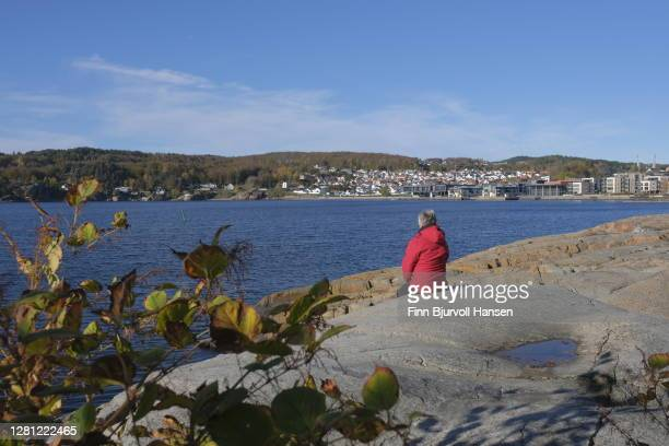 woman in red jacket sitting on a rock looking at the sea and the city - finn bjurvoll stock pictures, royalty-free photos & images