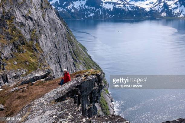 woman in red jacket sitting on the viewpoint of mountain hesten at senja in northern norway - finn bjurvoll stock-fotos und bilder