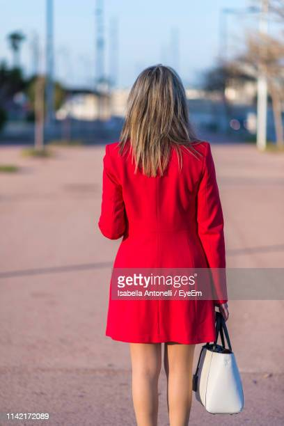 woman in red jacket standing on road - red jacket stock pictures, royalty-free photos & images