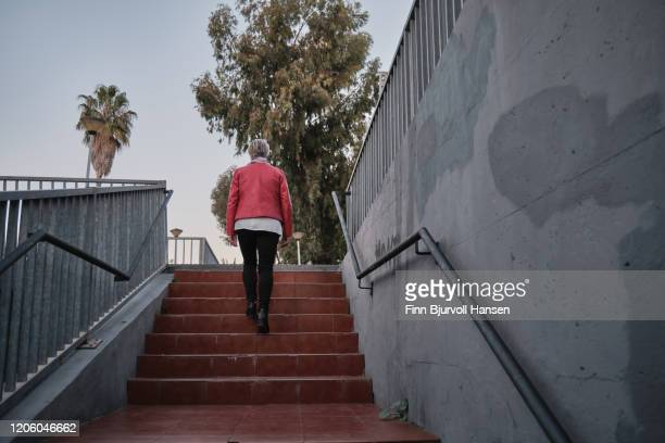 woman in red jacket walking up stairs - finn bjurvoll stock pictures, royalty-free photos & images