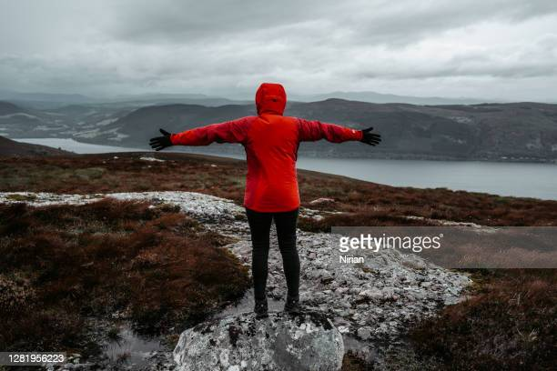 woman in red jacket with arms outstretched - scotland stock pictures, royalty-free photos & images