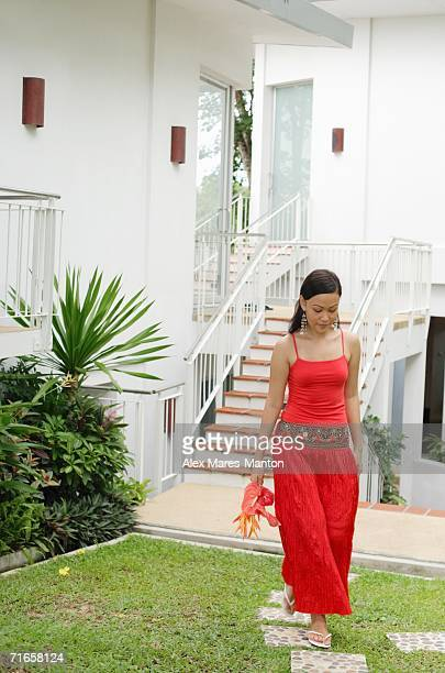 Woman in red outfit, holding flowers, walking through garden