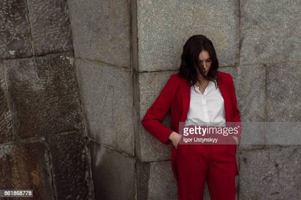 woman in red pantsuit standing near the brick wall - pant suit stock pictures, royalty-free photos & images