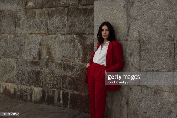 Woman in red pantsuit  walking in the city