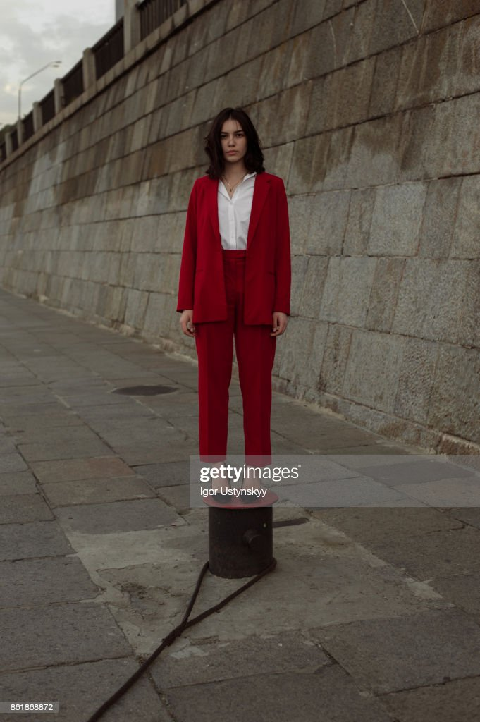 Woman in red pantsuit  walking in the city : Stock Photo