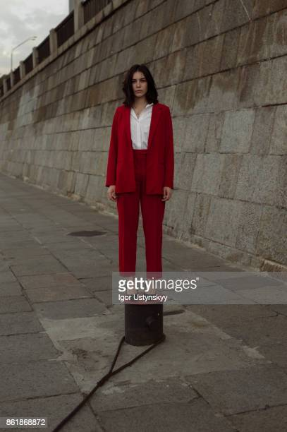 woman in red pantsuit  walking in the city - pant suit stock pictures, royalty-free photos & images
