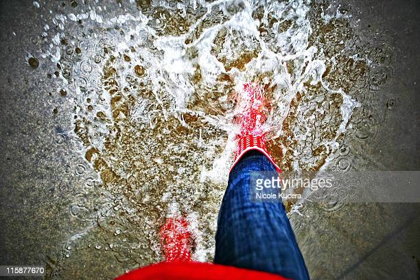 woman in red rain boots splashing flooded street - gummistiefel frau stock-fotos und bilder