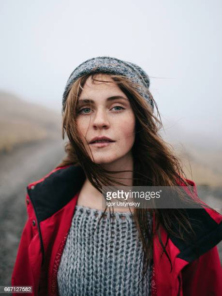 Woman in red raincoat in foggy mountains