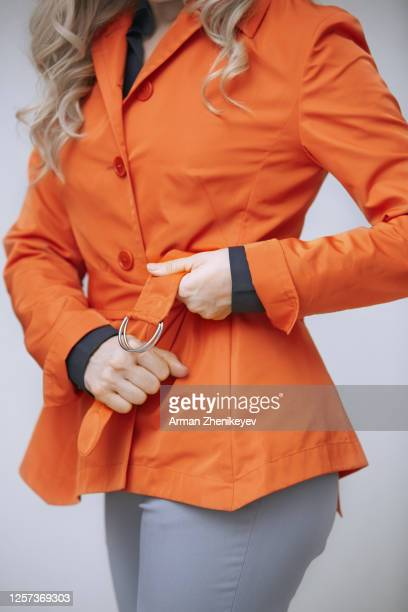 woman in red raincoat standing at the wall and tying belt - tighten stock pictures, royalty-free photos & images